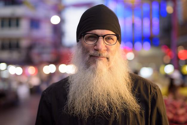Twarz dojrzały, brodaty turysta mężczyzna w okularach w chinatown w nocy