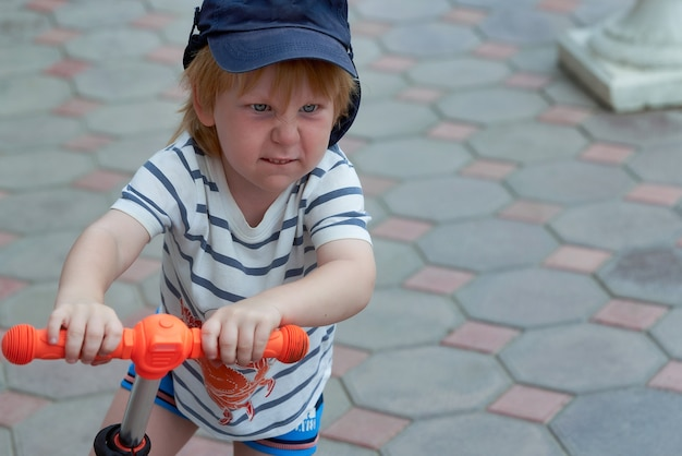 Twarz dziecka z jasną emocją na twarzy hulajnogi