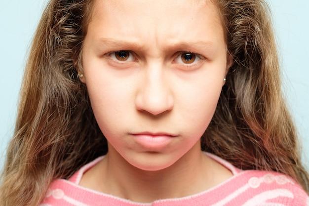 Twarz emocji. marszczące brwi, zrzędliwe dziecko z zaciśniętymi ustami i przenikliwym spojrzeniem. portret dziewczyny.