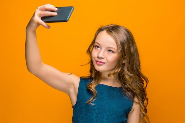 Twarz figlarnie szczęśliwa dziewczyna nastolatka z telefonem