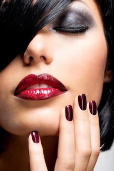 Twarz kobiety o pięknych ciemnych paznokciach i seksownych czerwonych ustach. modelka z czarnymi włosami