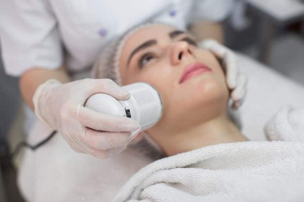 Twarz kobiety otrzymującej kosmetyki przeciwstarzeniowe przy użyciu ultradźwiękowej kawitacji