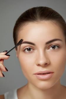 Twarz kobiety z bliska uroda makro oczy usta. odcień skóry. korekcja brwi