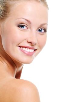 Twarz kobiety z ładnym uśmiechem i zdrową, piękną, jasną skórą na białych deseniach