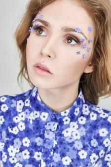 Twarz kobiety z niebieskimi kwiatami, dziewczyna w niebieskiej sukience kwiatowej. pielęgnacja skóry, czysta skóra, kosmetyki naturalne, remedium na zmarszczki. sztuka pielęgnacji urody, glamour