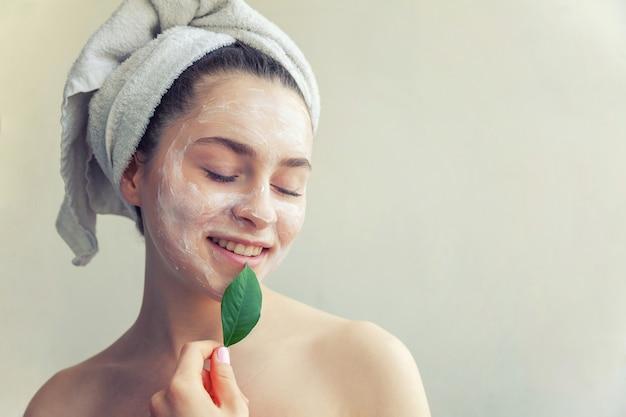 Twarz kobiety z zielonych liści i krem lub maska odżywcza