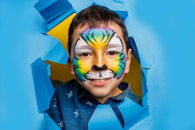 Twarz małego chłopca z farbą na twarzy, urodzinowy makijaż tygrysa lub ponura impreza odizolowana na niebieskiej ścianie