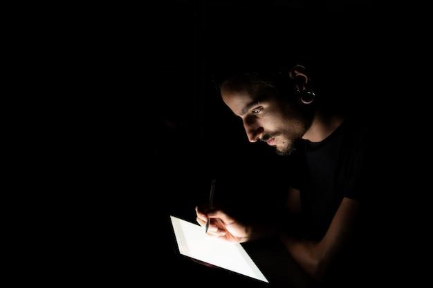 Twarz mężczyzny oświetlona ekranem tabletu podczas korzystania z pióra cyfrowego