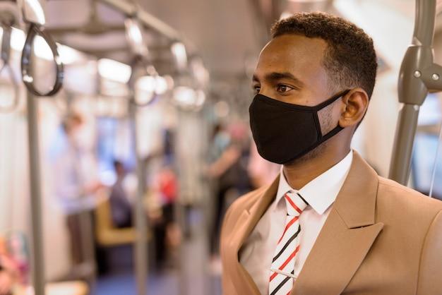 Twarz młodego biznesmena afrykańskiego noszenie maski i stojącej z odległością wewnątrz pociągu