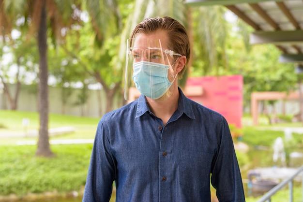 Twarz młodego mężczyzny myślącego podczas noszenia maski i osłony twarzy w celu ochrony przed wybuchem koronawirusa w parku