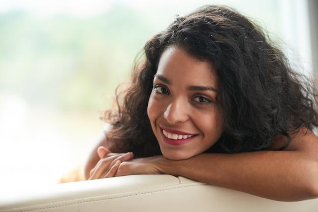 Twarz młodej atrakcyjnej brunetki uśmiecha się do kamery