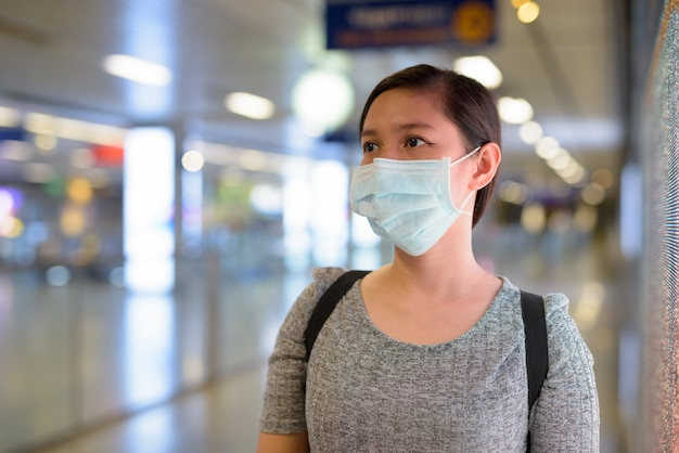 Twarz młodej azjatki noszącej maskę w celu ochrony przed epidemią koronawirusa na stacji metra