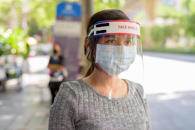 Twarz młodej azjatyckiej kobiety noszącej maskę i osłonę twarzy, czekając na przystanku autobusowym