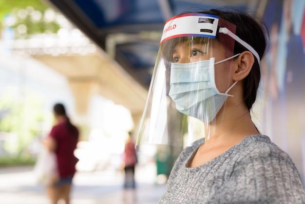 Twarz młodej azjatyckiej kobiety noszącej maskę i osłonę twarzy siedząc na przystanku autobusowym