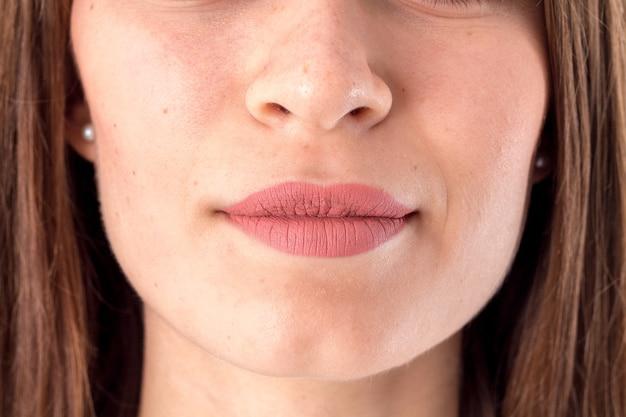 Twarz młodej dziewczyny, na której widoczny jest zbliżenia nosa i ust