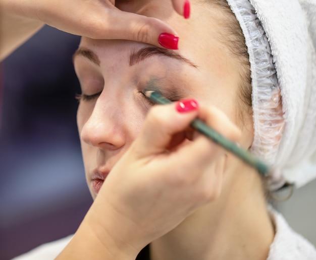 Twarz młodej dziewczyny z rąk wizażystki stosowania makijażu