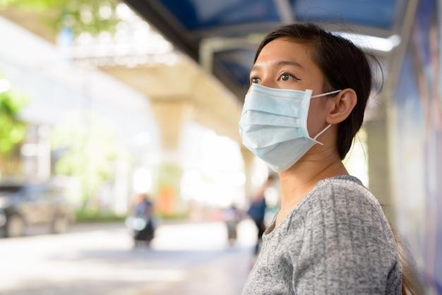 Twarz młodej kobiety z azji z maską myśli siedząc na przystanku autobusowym