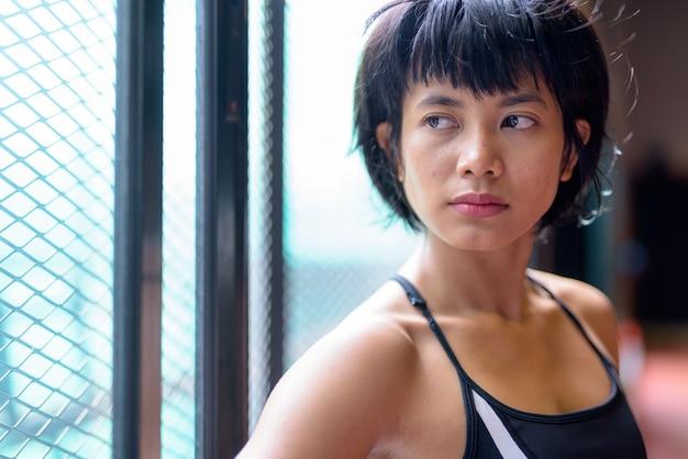 Twarz młodej pięknej kobiety azji myśli na siłowni