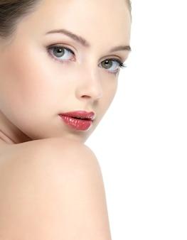 Twarz młodej pięknej kobiety z czystą skórą i jaskrawoczerwoną szminką na ustach