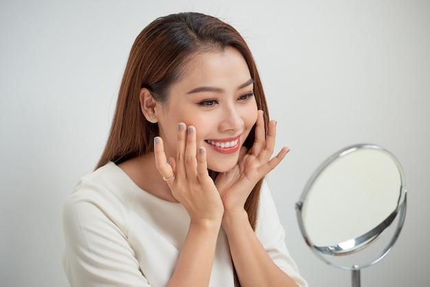 Twarz młodej pięknej zdrowej kobiety patrzącej w lustro