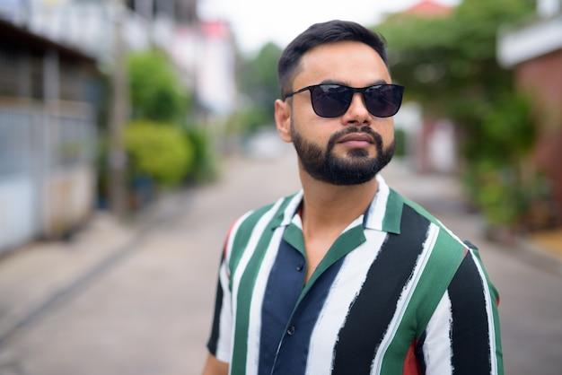 Twarz młody przystojny brodaty mężczyzna indyjski z okulary myśli na zewnątrz