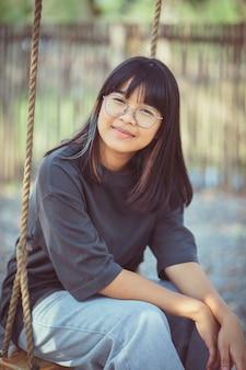 Twarz nastolatka azjatyckiego na huśtawce liny