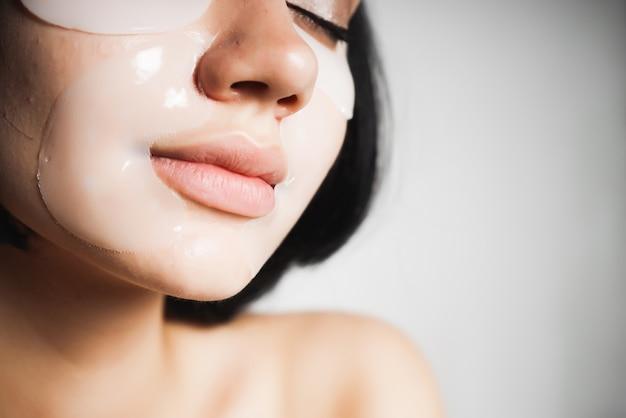 Twarz pięknej czarnowłosej dziewczyny, która pielęgnuje skórę, zamknęła oczy.