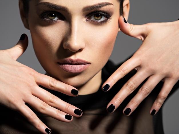 Twarz pięknej dziewczyny z makijażem mody i czarnymi paznokciami, pozowanie na ciemnej ścianie