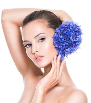 Twarz pięknej dziewczyny z niebieskimi kwiatami posy fild