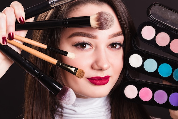 Twarz pięknej dziewczyny ze szczotkami do makijażu i cieni do powiek na czarnej ścianie