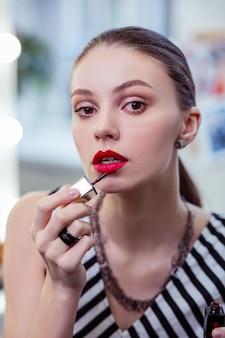Twarz pięknej młodej kobiety nakładającej szminkę