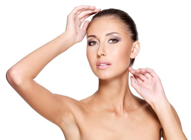 Twarz pięknej młodej kobiety o zdrowej skórze, która się dotyka