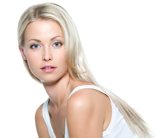 Twarz pięknej młodej kobiety z czystą skórą na białej ścianie