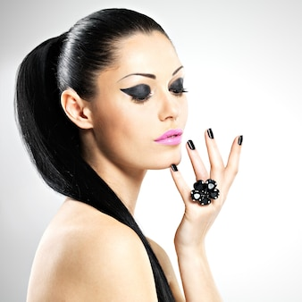 Twarz pięknej seksownej kobiety z czarnymi paznokciami i różowymi ustami. sexy dziewczyna z makijażem mody