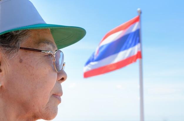 Twarz po stronie starych kobiet tajowie i flaga tajlandii na niebieskim tle nieba