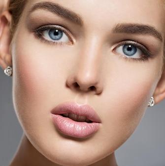 Twarz ślicznej dziewczyny o niebieskich oczach sexy. portret pięknej młodej kobiety z brązowym makijażem. twarz modelka o niebieskich oczach.