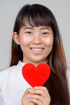 Twarz szczęśliwa młoda kobieta azjatyckich gospodarstwa serce gotowe na walentynki