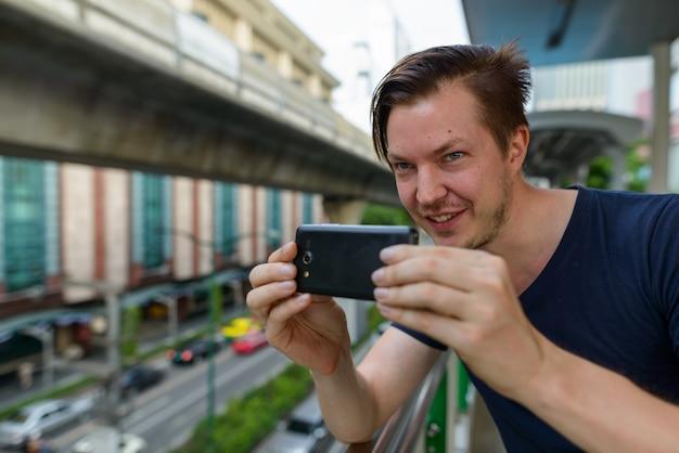 Twarz szczęśliwy młody przystojny mężczyzna robi zdjęcie z telefonu na dworcu nieba