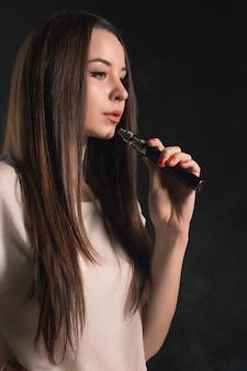 Twarz vaping młodej kobiety w czarnym studio