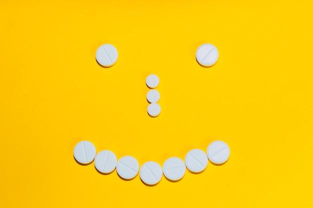 Twarz z uśmiechem wyłożona tabletkami i witaminami na żółtym tle. widok z góry