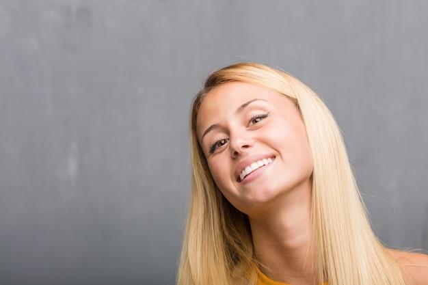 Twarz zbliżenie, portret naturalnej młodej blondynki kobiety rozochoconej iz dużym uśmiechem, ufnym
