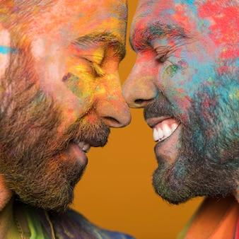 Twarzą w twarz para szczęśliwych homoseksualnych mężczyzn w kolorowej farbie