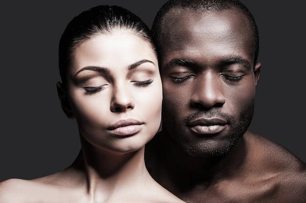 Twarzą w twarz. portret bez koszuli afrykańskiego mężczyzny i kaukaskiej kobiety, którzy łączą ze sobą twarze i mają zamknięte oczy, stojąc na szarym tle