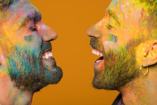 Twarze śmiejących się gejów zabrudzonych farbą