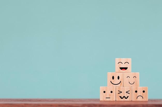 Twarze z różnymi emocjami na drewnianych klockach ostrosłupowych na drewnianym stole i niebieskim tle