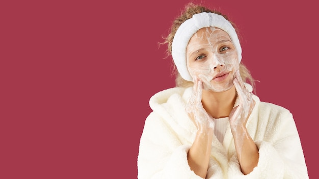 Twarzowy. dziewczyna w szlafroku frotte i masce na twarzy