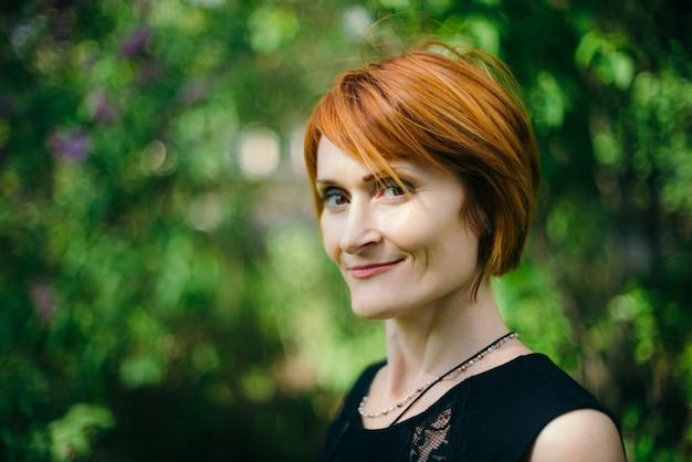 Twarzy portret zadziwiająca uśmiechnięta kobieta z czerwonym włosy w czerni sukni z kopii przestrzenią na zieleni