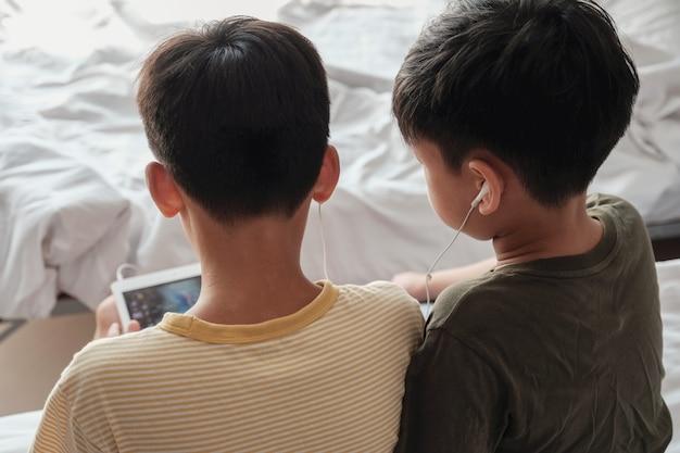 Tween chłopcy używający tabletu i udostępniający słuchawki, słuchający muzyki, grający w gry, wykorzystujący technologię internetową