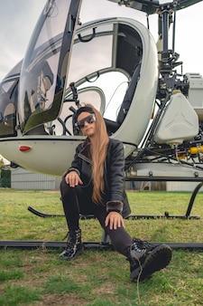 Tween dziewczyna siedzi na podnóżku otwartego helikoptera