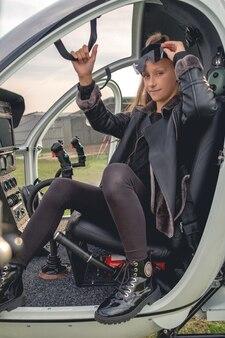 Tween dziewczyna siedzi w kokpicie lekkiego helikoptera
